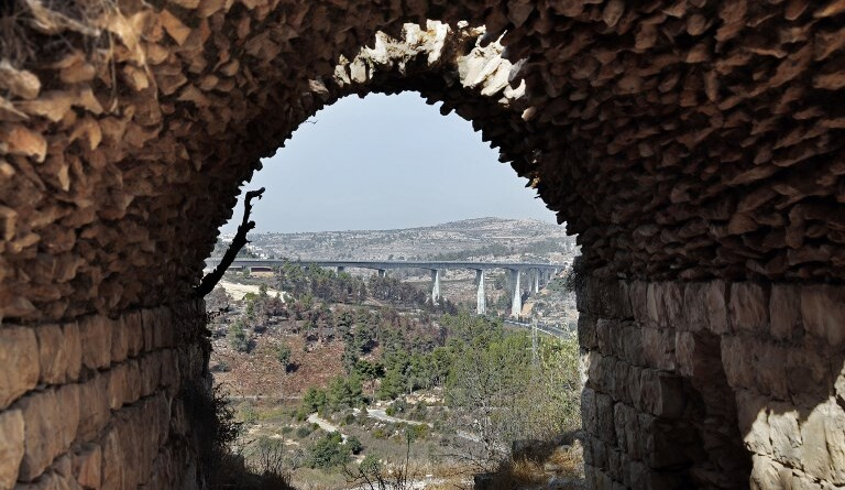 A picture taken from inside an old house in Palestinian village of Lifta which was abandoned during fighting in the 1948 Arab-Israeli war, shows the bridge for a new train line on the outskirts of Jerusalem, on October 20, 2017. Lifta is one of the few intact abandoned Palestinian villages has been named by the World Monuments Fund as one of 25 at-risk sites around the world. According to the New York-based nonprofit group, Lifta has no parallel anywhere in the Middle East. The World Monuments Fund, which publishes its list every two years, was among voices blocking the building of a luxury real estate project at the site. / AFP PHOTO / THOMAS COEX